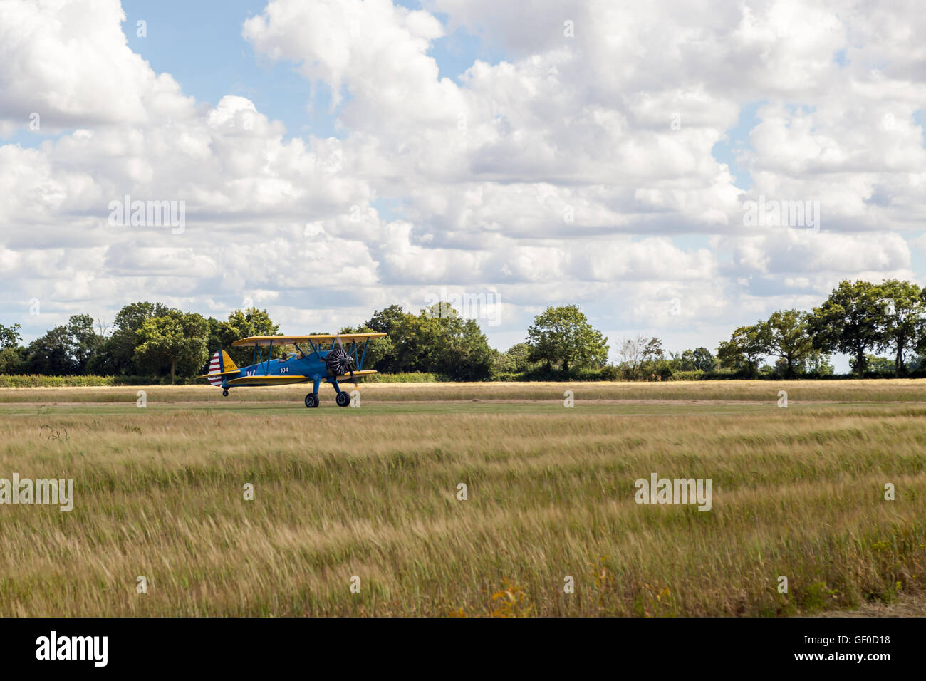A vintage bi-plane taking off from grass runway Stock Photo