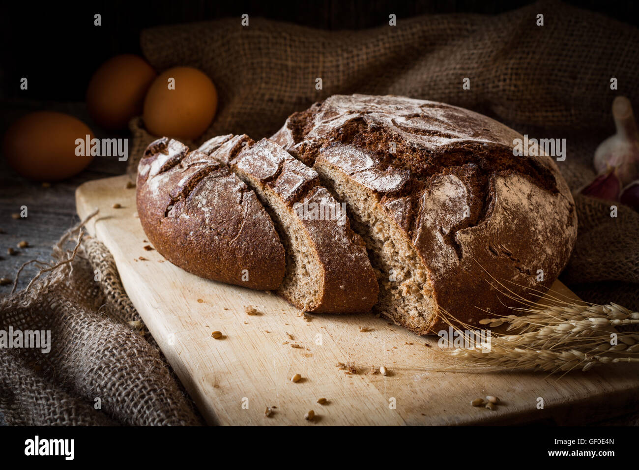 Sourdough rye bread sliced on wooden cutting board. Rustic still life. Natural light, low key - Stock Image
