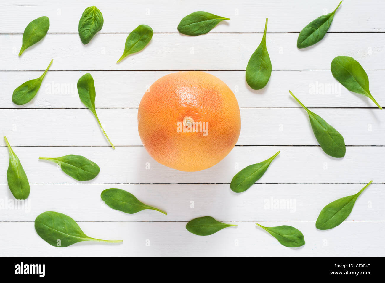 Fruit pattern. Spinach leaves and red grapefruit on white wooden planks background. Flat lay of fresh healthy food - Stock Image