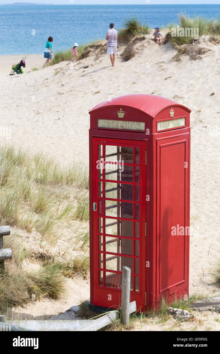 Red telephone box by Studland beach with family enjoying the seaside in the distance in July - Stock Image