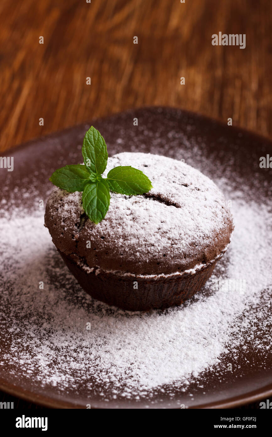 Homemade chocolate pudding with fondant center , lava cake on wooden background - Stock Image