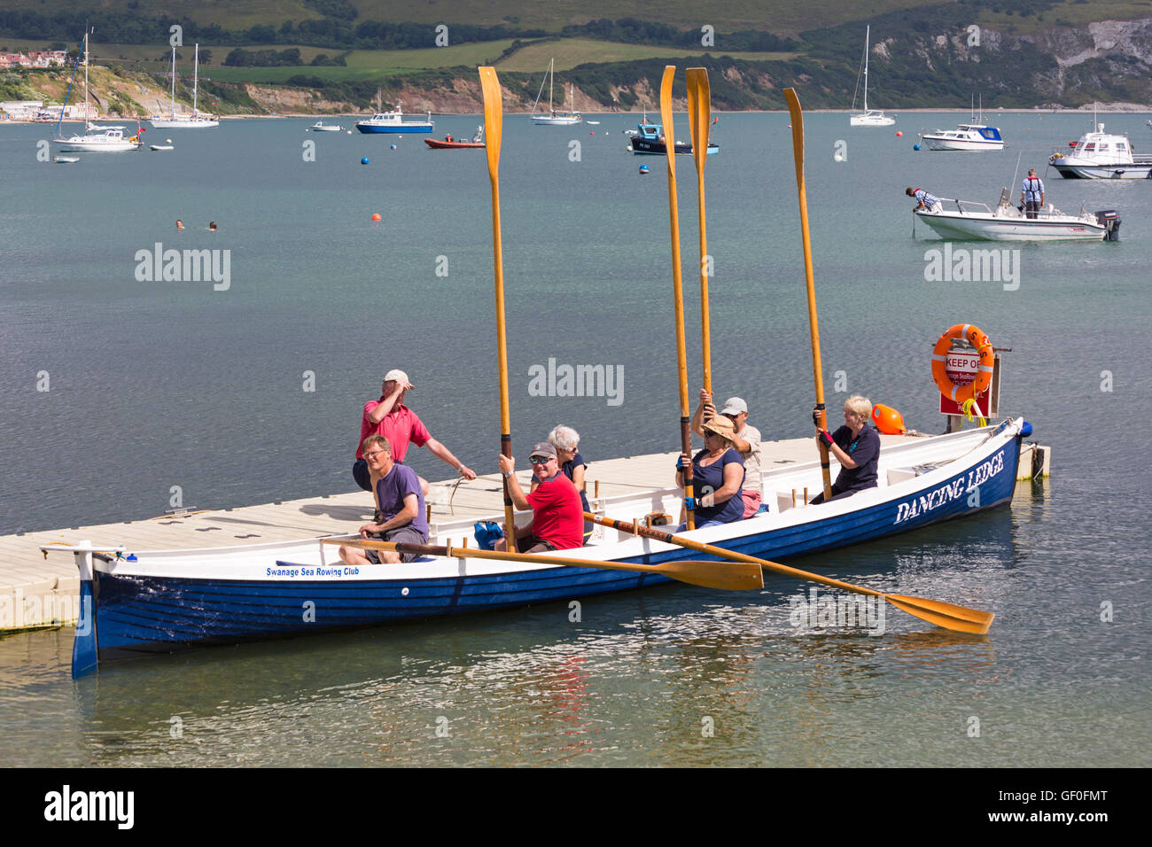 Swanage Sea Rowing Club in Dancing Ledge gig holding oars up at Swanage in July - Stock Image