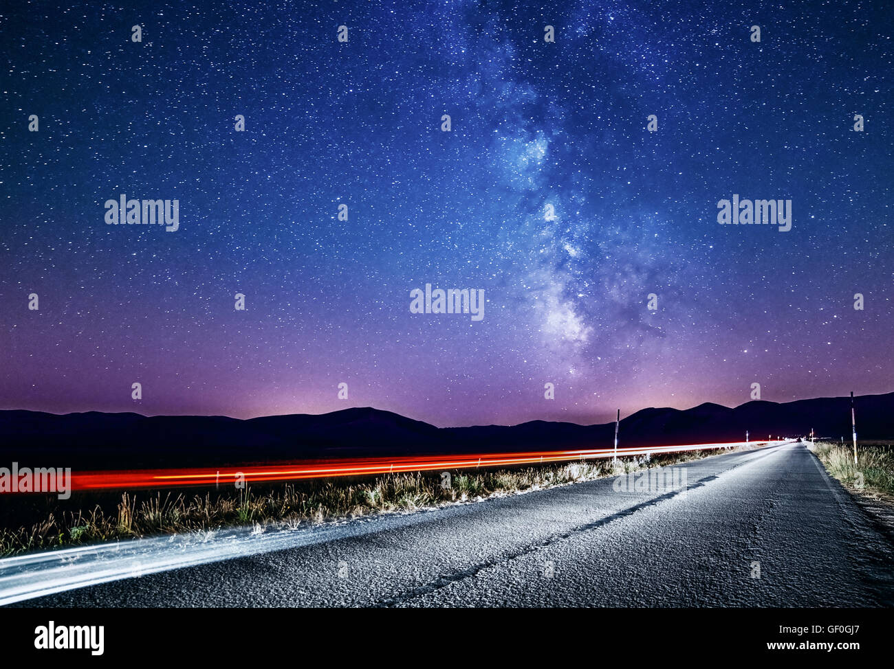 Night sky with milky way and stars. Night road illuminated by car. Light trails - Stock Image