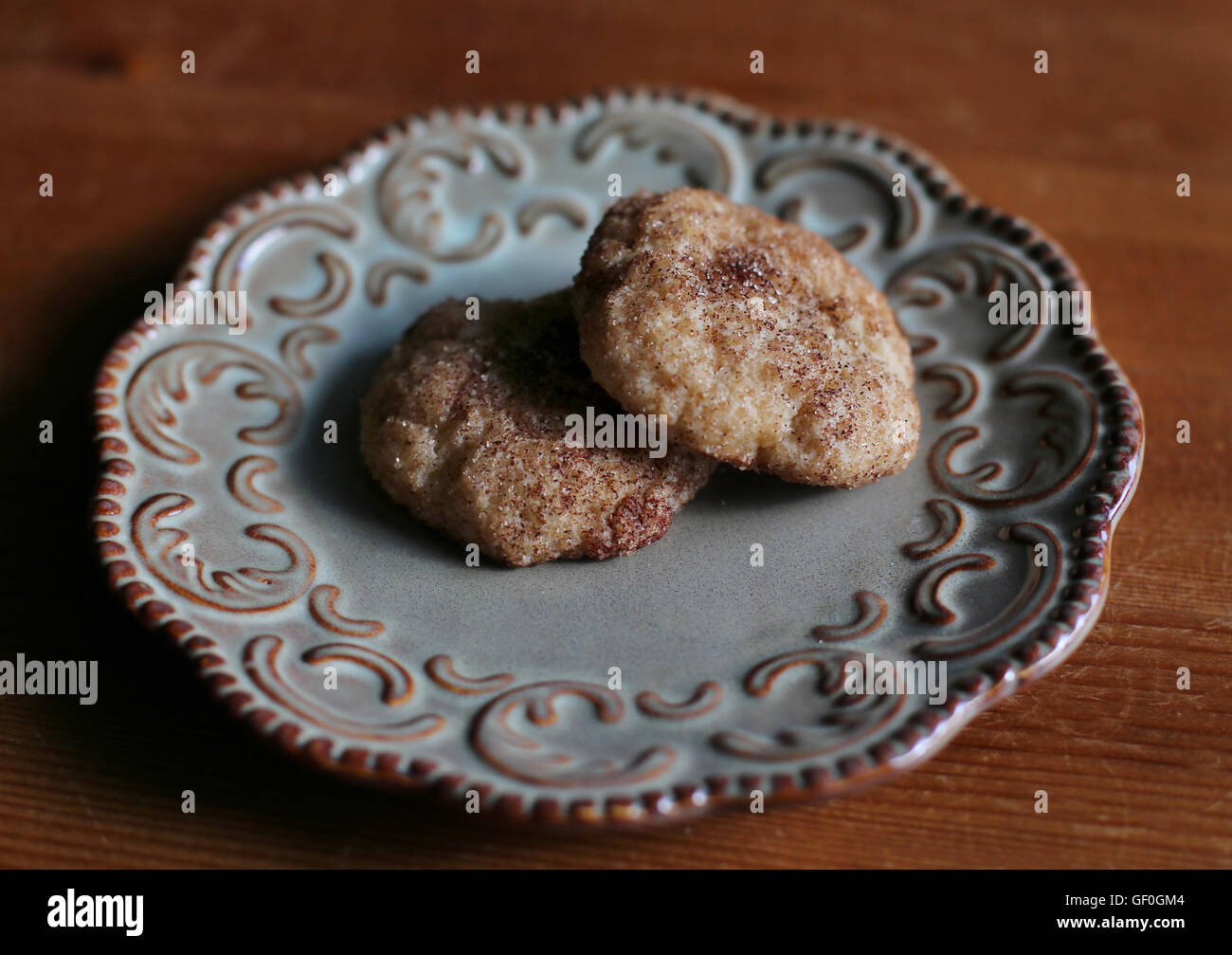 Two snickerdoodle cookies on a plate. - Stock Image