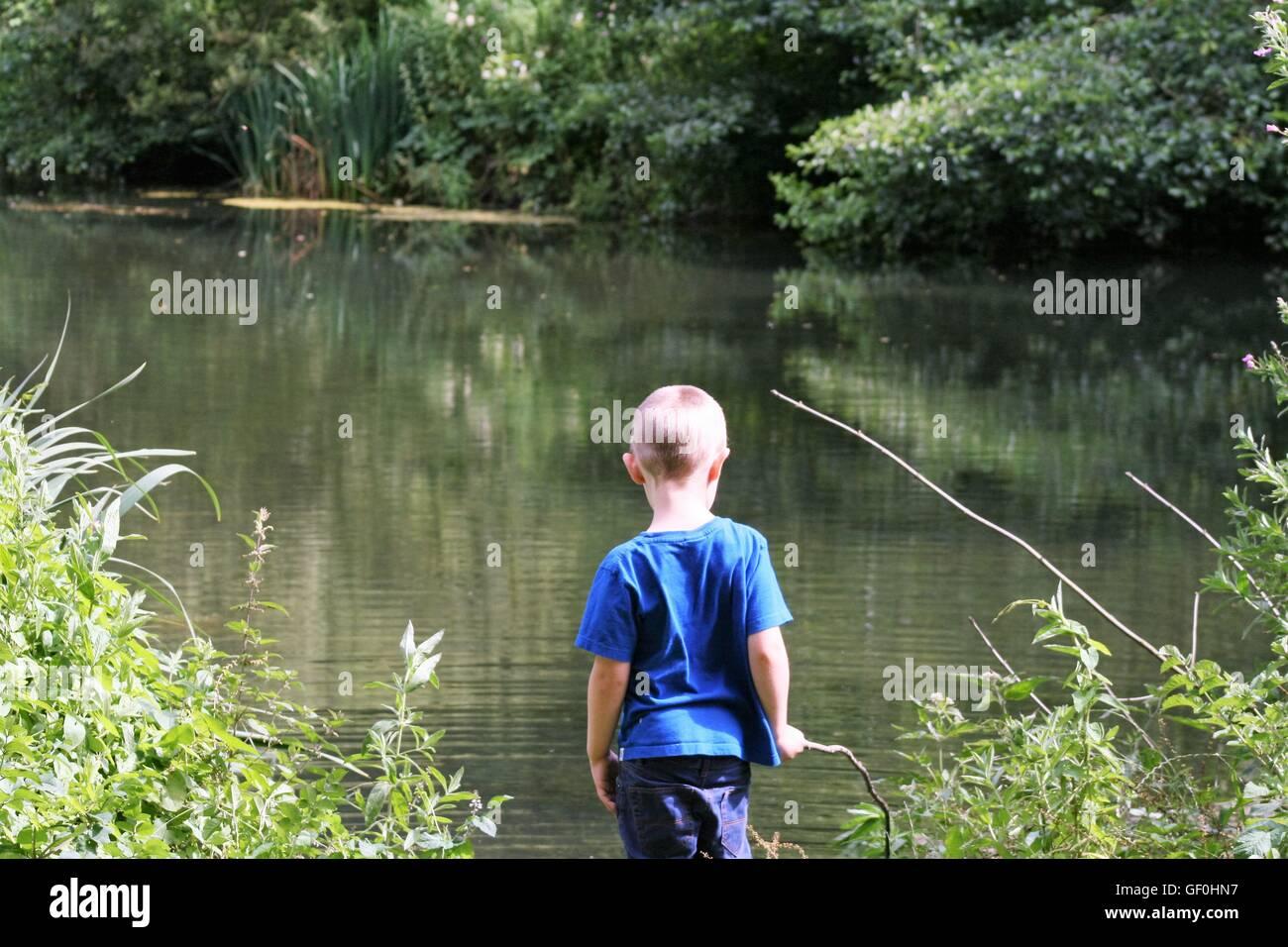 Boy stood at lake - Stock Image