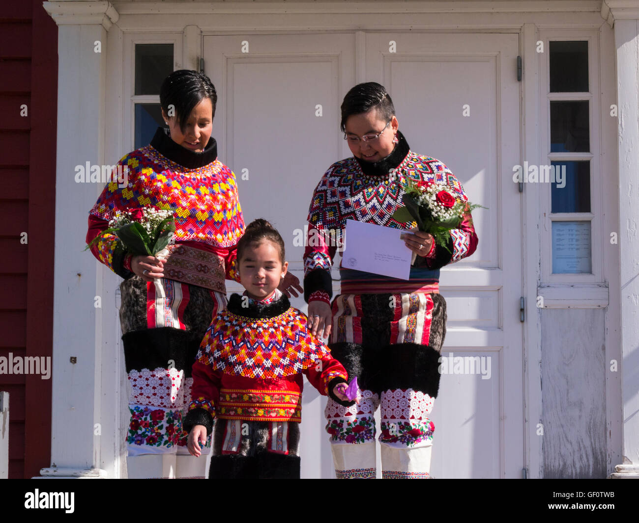 Two women posing with young relative in National dress for gay marriage wedding photo in front of Nuuk Cathedral - Stock Image