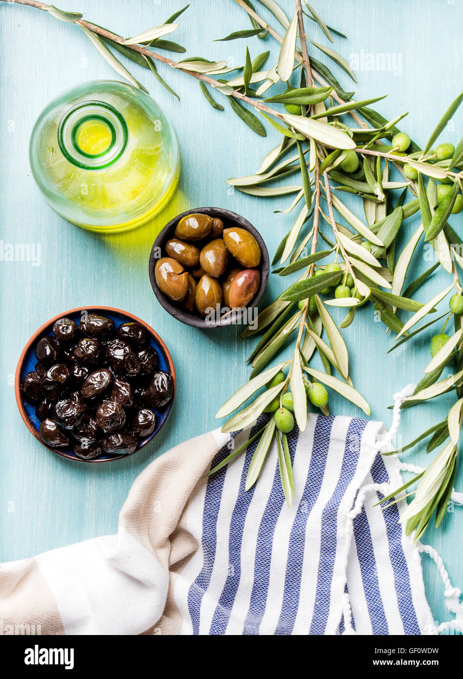 Two bowls with pickled green and black olives, olive tree sprigs, fresh homemade oil over blue Turquoise background - Stock Image