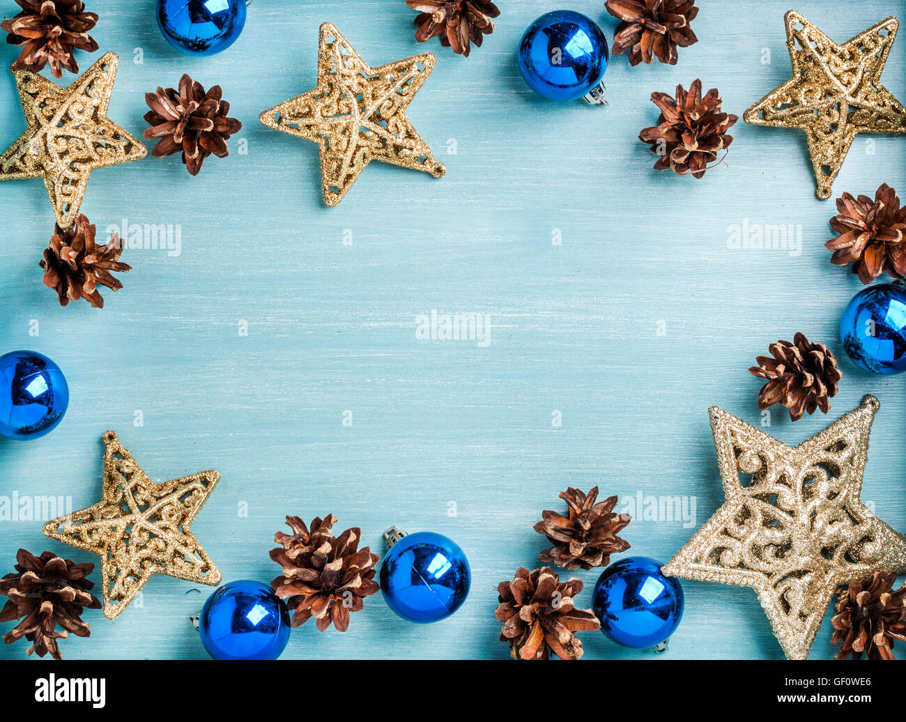 New Year or Christmas background: golden stars, blue glass balls and cones over turquoise wooden backdrop, copy Stock Photo