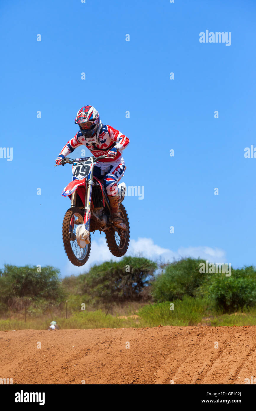 Motocross rider and bike clearing a tabletop jump during the final heat of the race - Stock Image