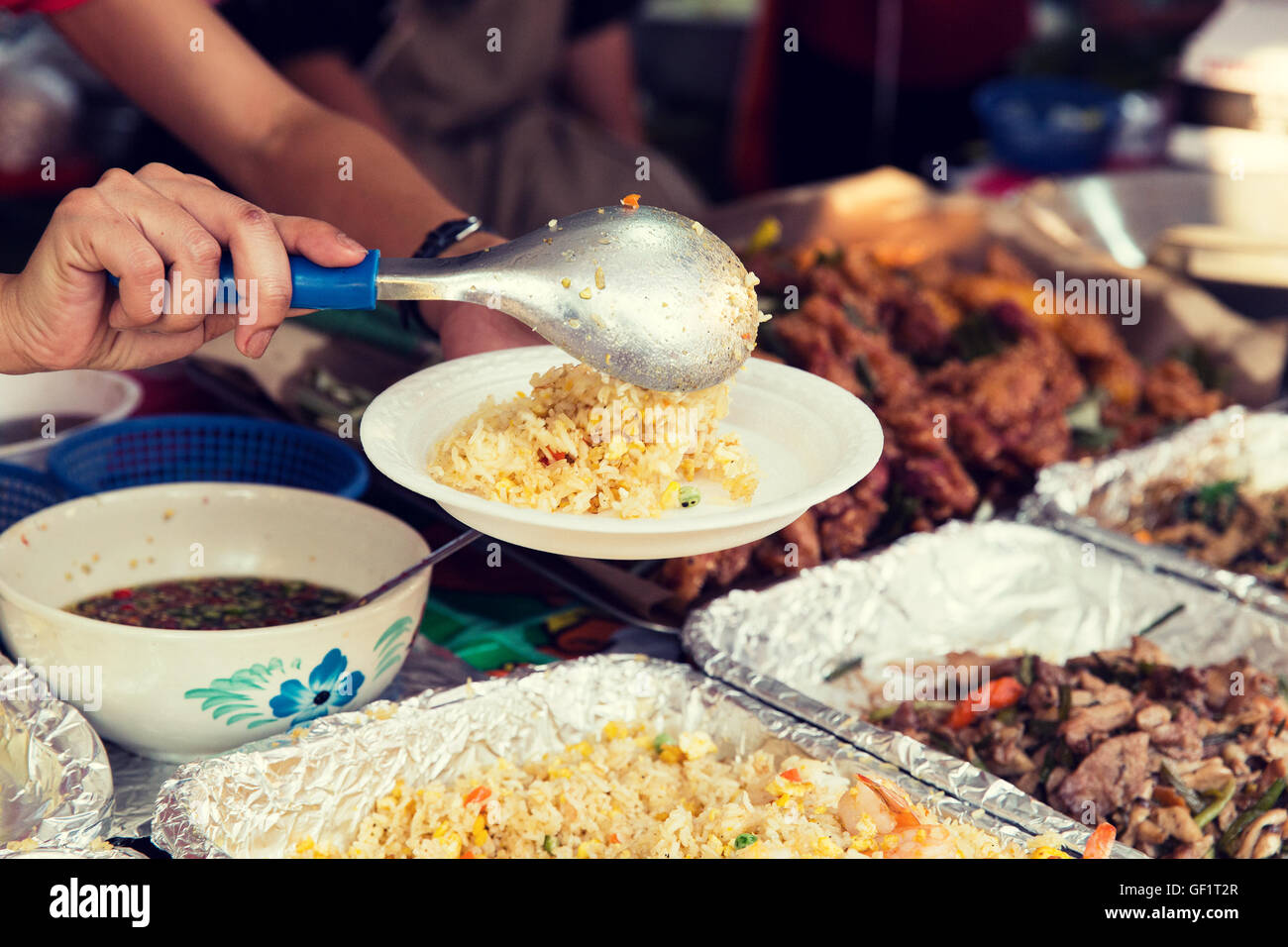 close up of hands with wok at street market - Stock Image