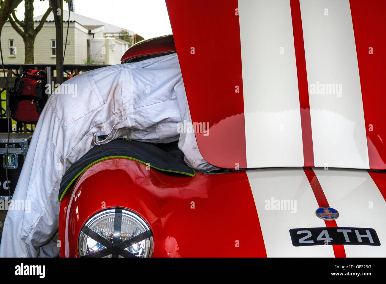 Mechanic leans into the engine compartment of the 1963 AC Cobra of Martin Hunt in the paddock, 2015 Goodwood Revival, - Stock Image