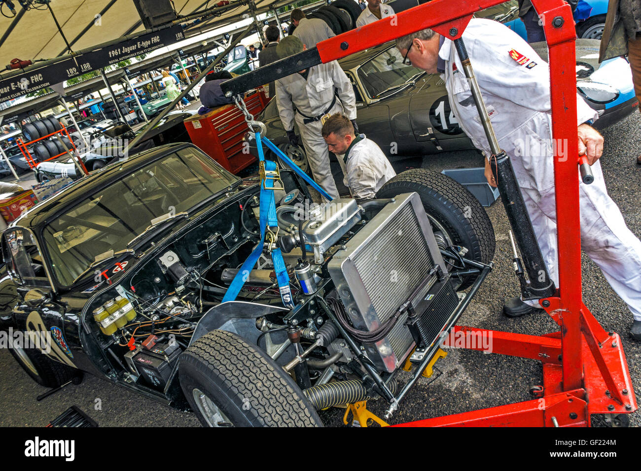 Mechanics prepare the 1962 Jaguar E-Type FHC in the paddock at the 2015 Goodwood REvival, Sussex, UK. - Stock Image