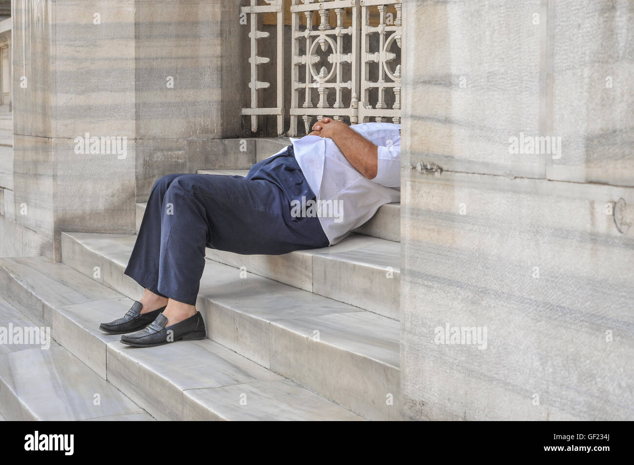 A man holds a midday nap on steps in Istanbul's historic quarter during the 2011 Ramadan. - Stock Image