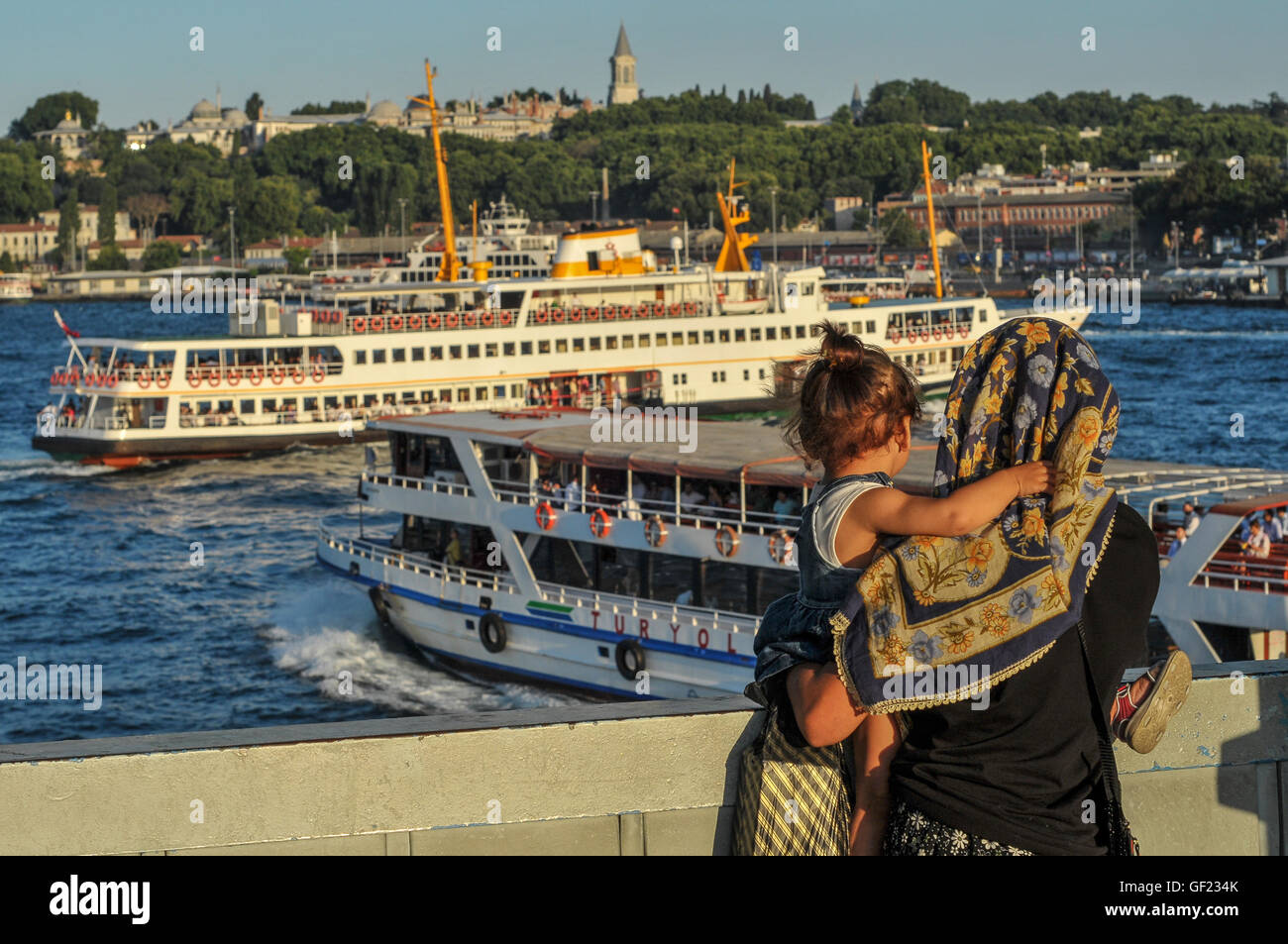 A woman and child watch ferry boats on the Golden Horn, from Galata bridge.  Topkapi Palace can be seen in the distance - Stock Image