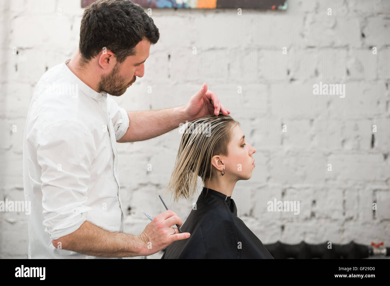 hairdresser cuts hair with scissors on crown of handsome satisfied client in professional hairdressing salon - Stock Image