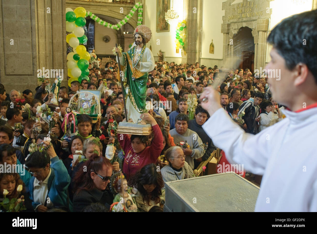 Worshipers with statues and other articles of devotion to Saint Jude Thaddeus, assist at a Mass in Mexico City. - Stock Image