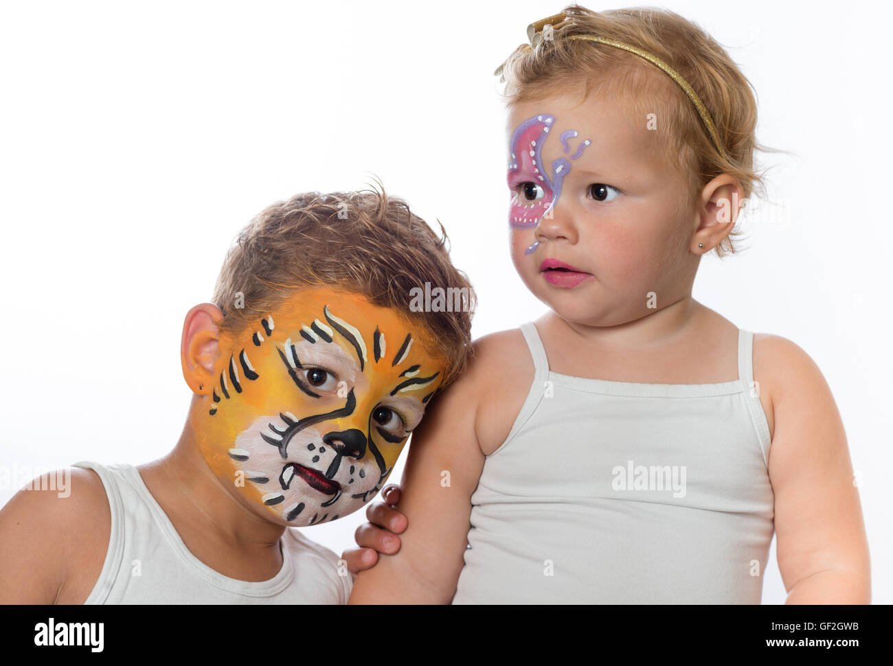 brother and sister with facepaintings of a tiger and a butterlfy - Stock Image