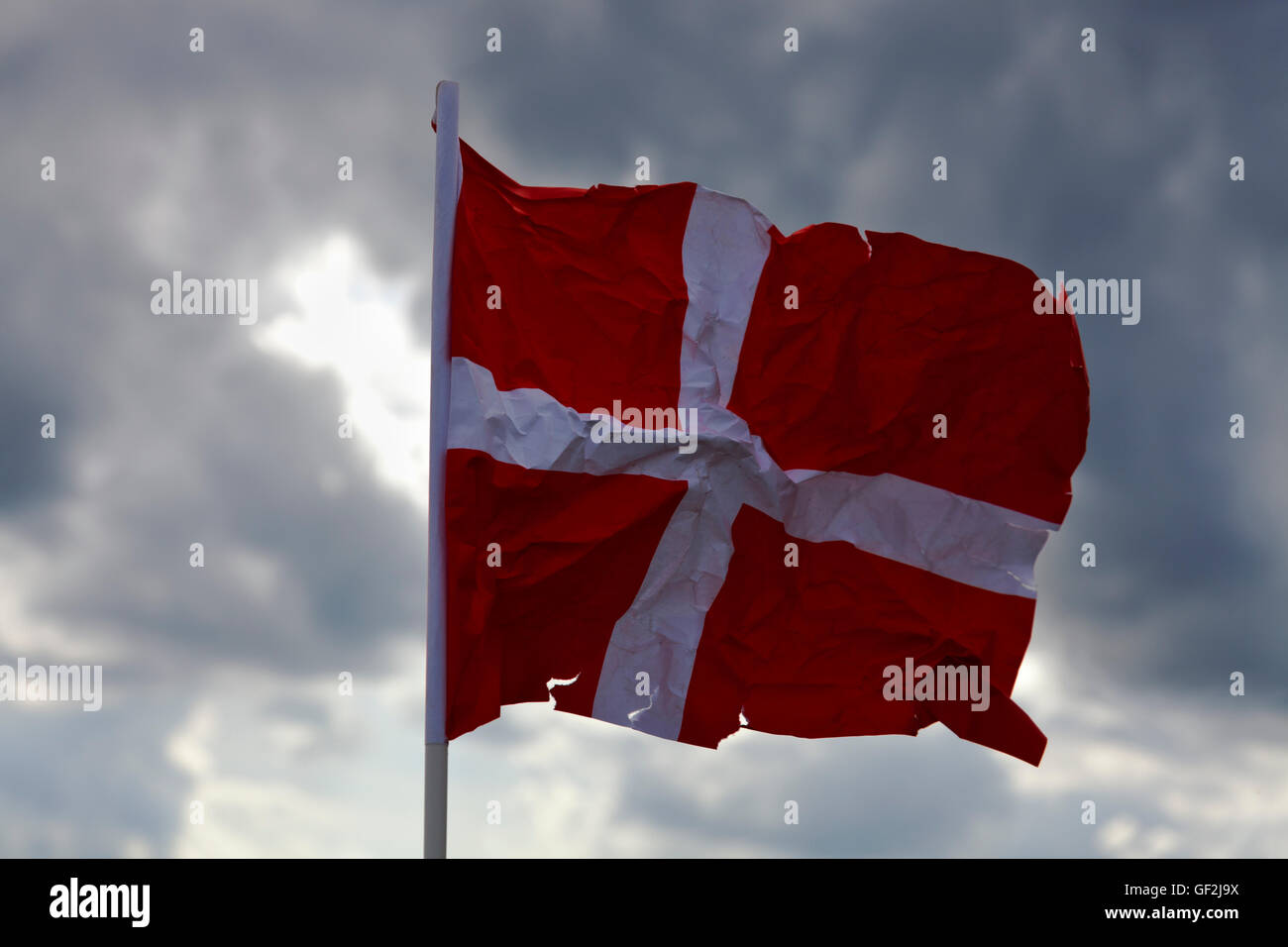 A crumpled and torn paper Dannebrog flag, the Danish flag against dark clouds. Close to being the happiest people? Stock Photo