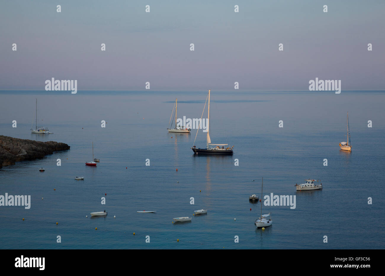 Sunrise over yachts anchored in Saint Elm harbor, Mallorca, Spain. - Stock Image