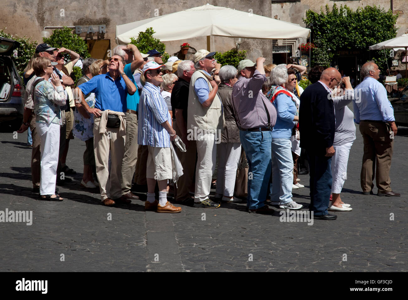 German tourists look at the Duomo on a tour in Orvieto, Italy while one man looks at something else? - Stock Image