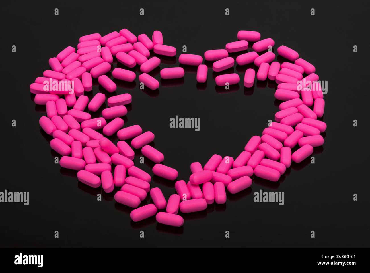 Migraine Pills pink capsules vitamins on black background - Stock Image