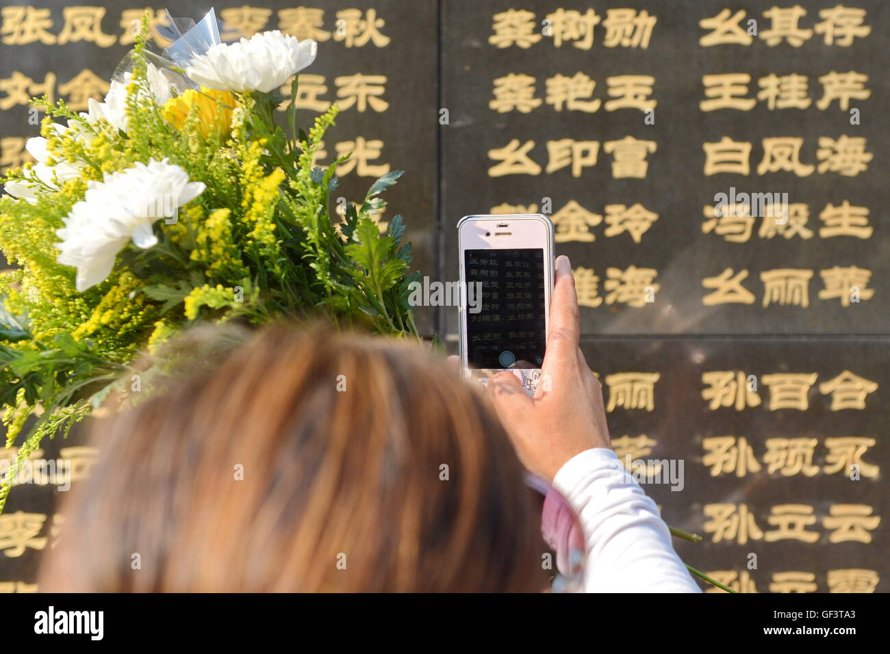 Tangshan, China's Hebei Province. 28th July, 2016. A woman takes photos of the name of her relative killed in - Stock Image