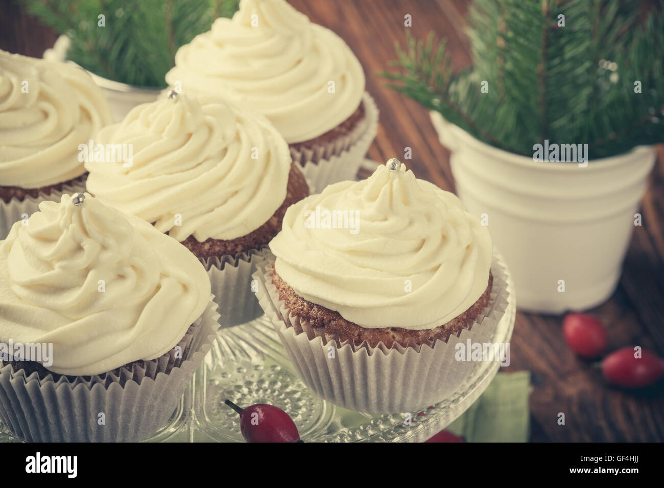 Homemade christmas cupcakes with cream cheese frosting on cake stand on wooden background with spruce twigs in ceramic - Stock Image