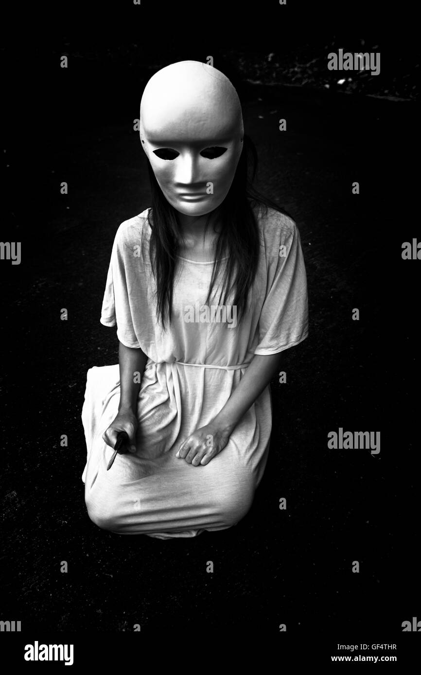 Dark doctrine,Mysterious woman wearing white mask,Scary background for book cover Stock Photo