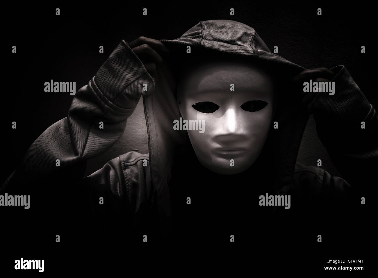 Dark doctrine,Mysterious woman wearing white mask under hoodie,Scary background for book cover - Stock Image