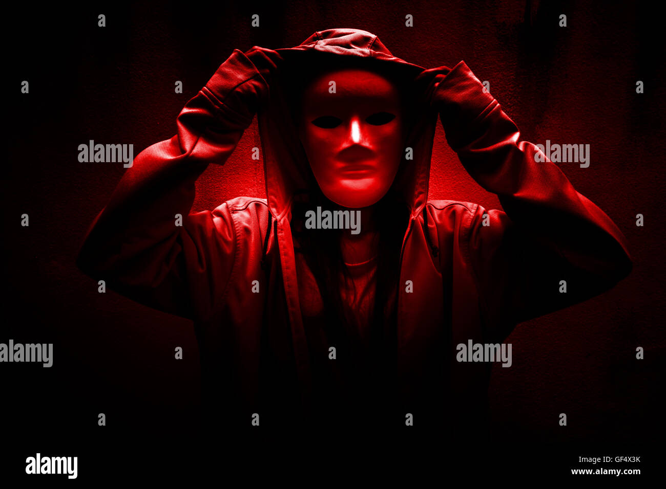 Dark doctrine,Mysterious woman wearing white mask under hoodie,Scary background for book cover Stock Photo