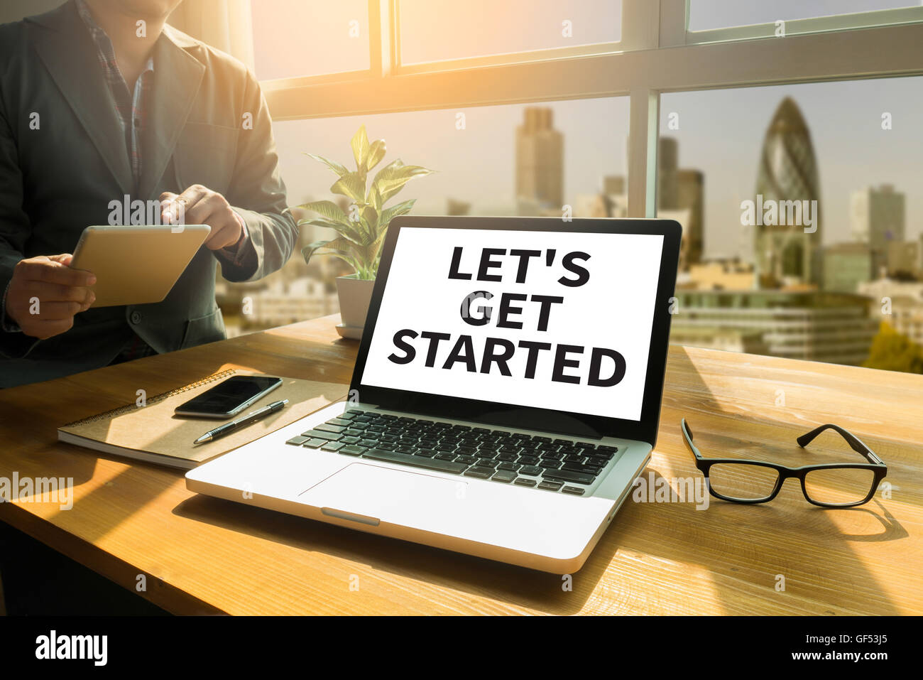 LET'S GET STARTED Thoughtful male person looking to the digital tablet screen, laptop screen,Silhouette and - Stock Image