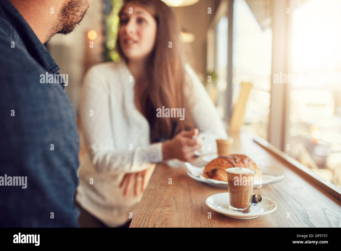 Cup of coffee and food on table with couple talking in background at cafe. - Stock Image