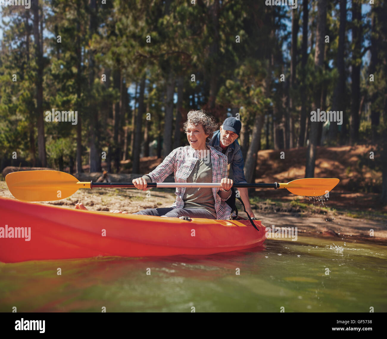 Portrait of happy mature couple having fun at the lake. Woman paddling kayak with man pushing from behind on a summer - Stock Image