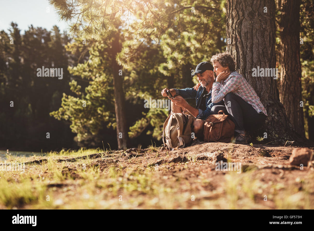 Smiling mature couple looking for directions with help of a compass. Senior couple hiking in forest. - Stock Image