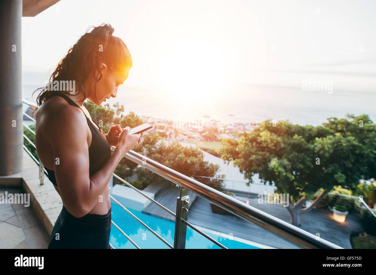 Side view of fitness woman standing in balcony and using mobile phone. Healthy female reading text message on the - Stock Image