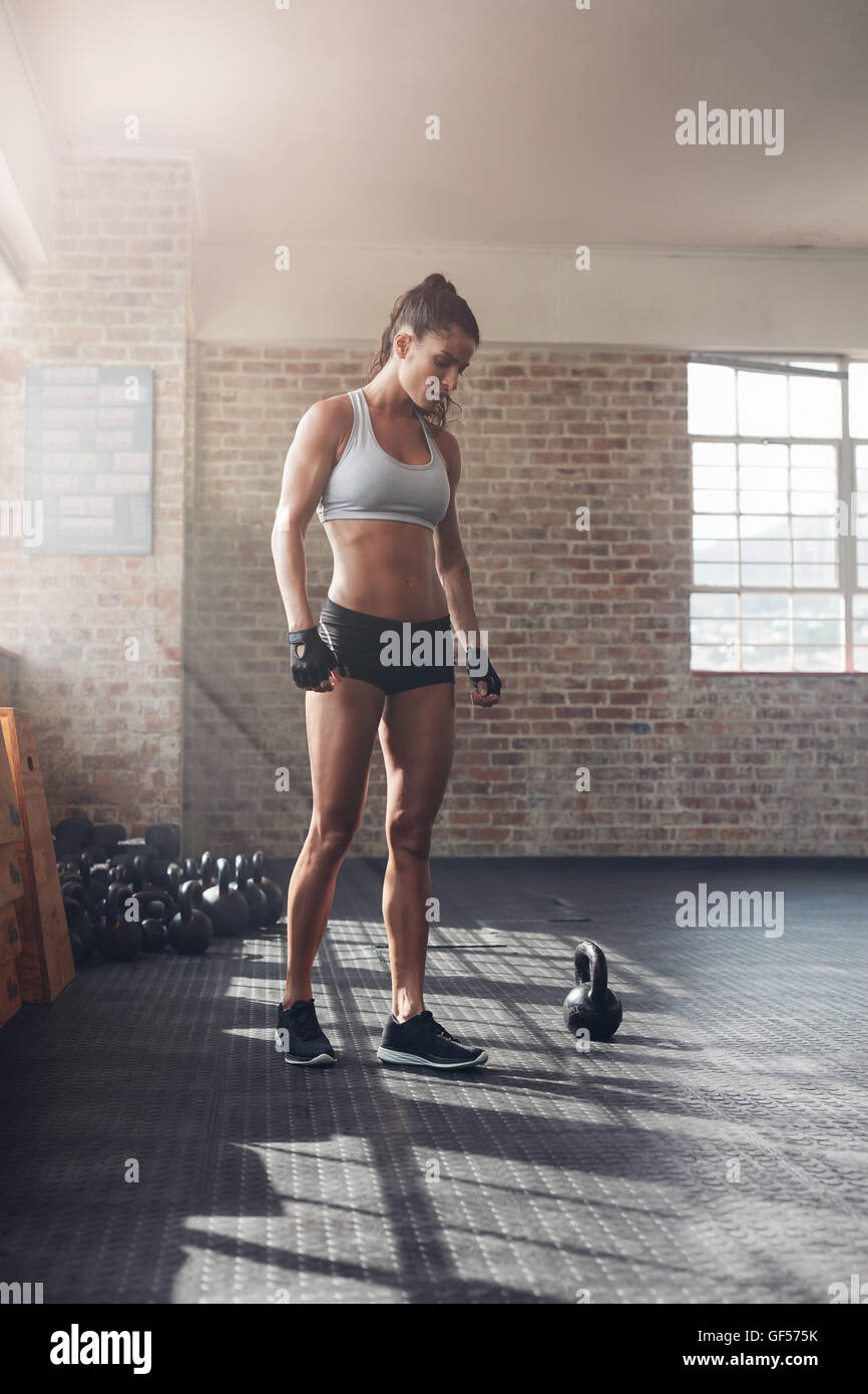 Full length shot of strong young woman in sportswear standing in gym. Tough female athlete at crossfit gym. - Stock Image