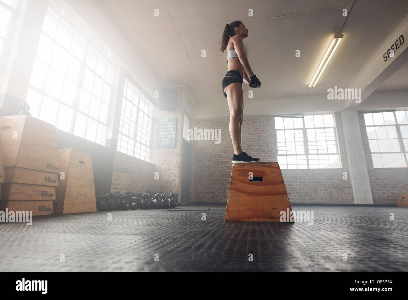 Low angle shot of fit young female model in sports wear standing on a box at gym. Muscular woman doing box jump - Stock Image