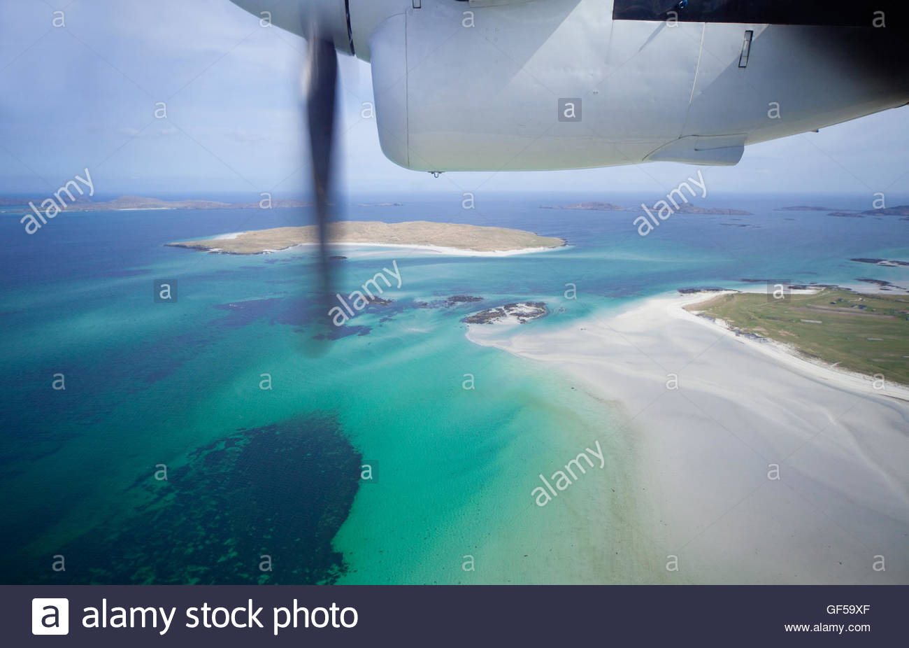 The view from the inter-island airplane as it flies over the Isle of Barra with the Isle of Fuday visible beyond, - Stock Image