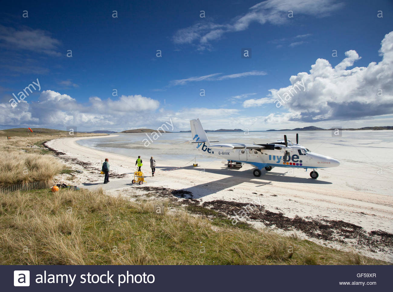 Passengers walking towards an aeroplane on Traigh Mhor Beach - the runway for the Isle of Barra Airport, Outer Hebrides. - Stock Image