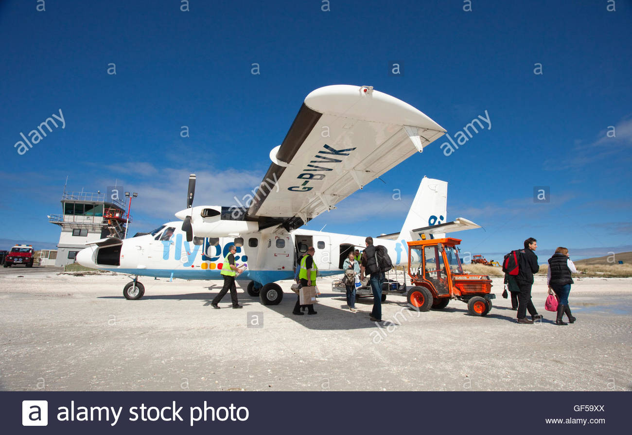 People disembark an aeroplane on Traigh Mhor Beach - the runway for the Isle of Barra Airport, Outer Hebrides. Scotland - Stock Image