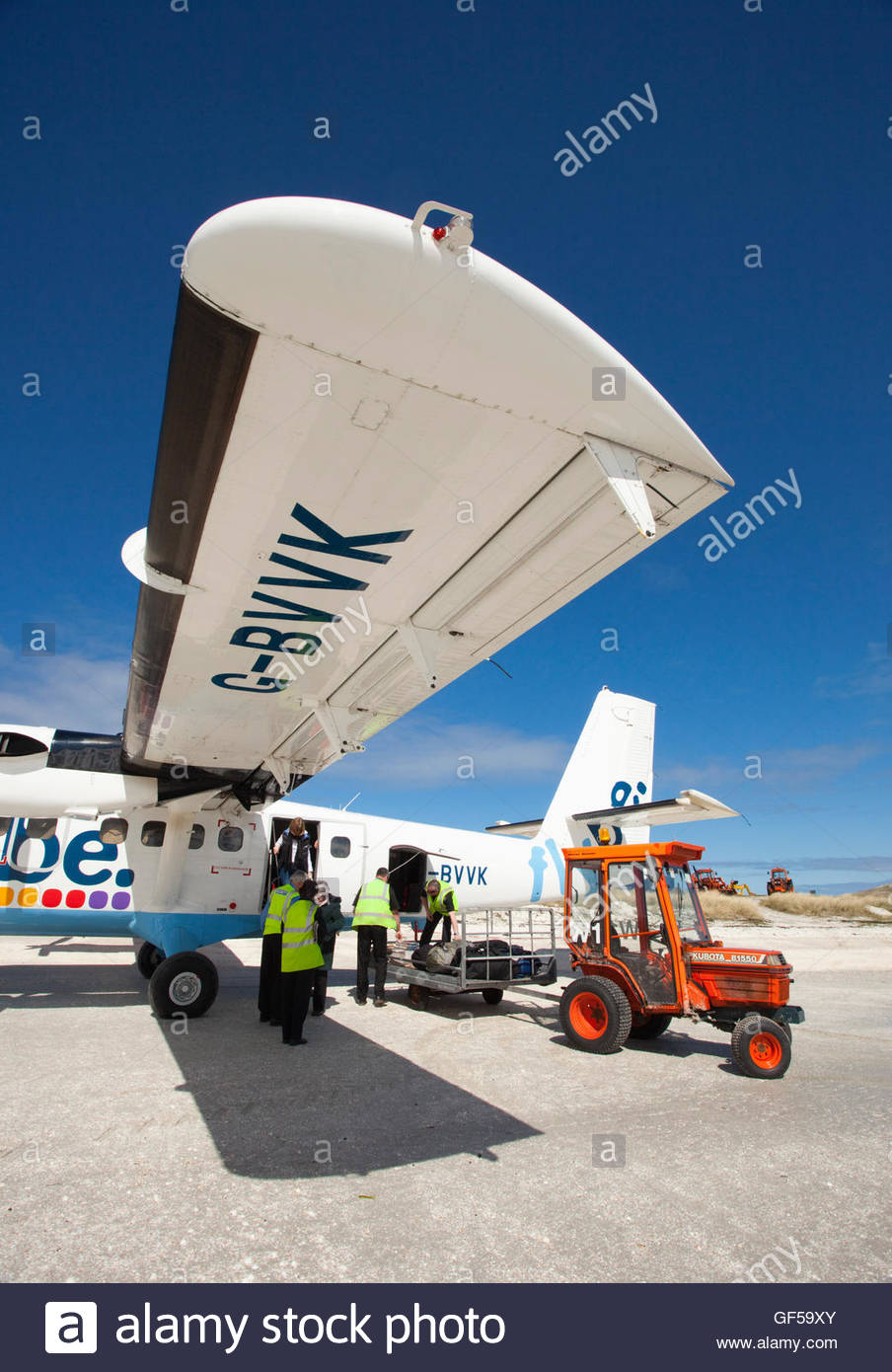 Unloading luggage from an aeroplane on Traigh Mhor Beach - the runway for the Isle of Barra Airport, Outer Hebrides. - Stock Image
