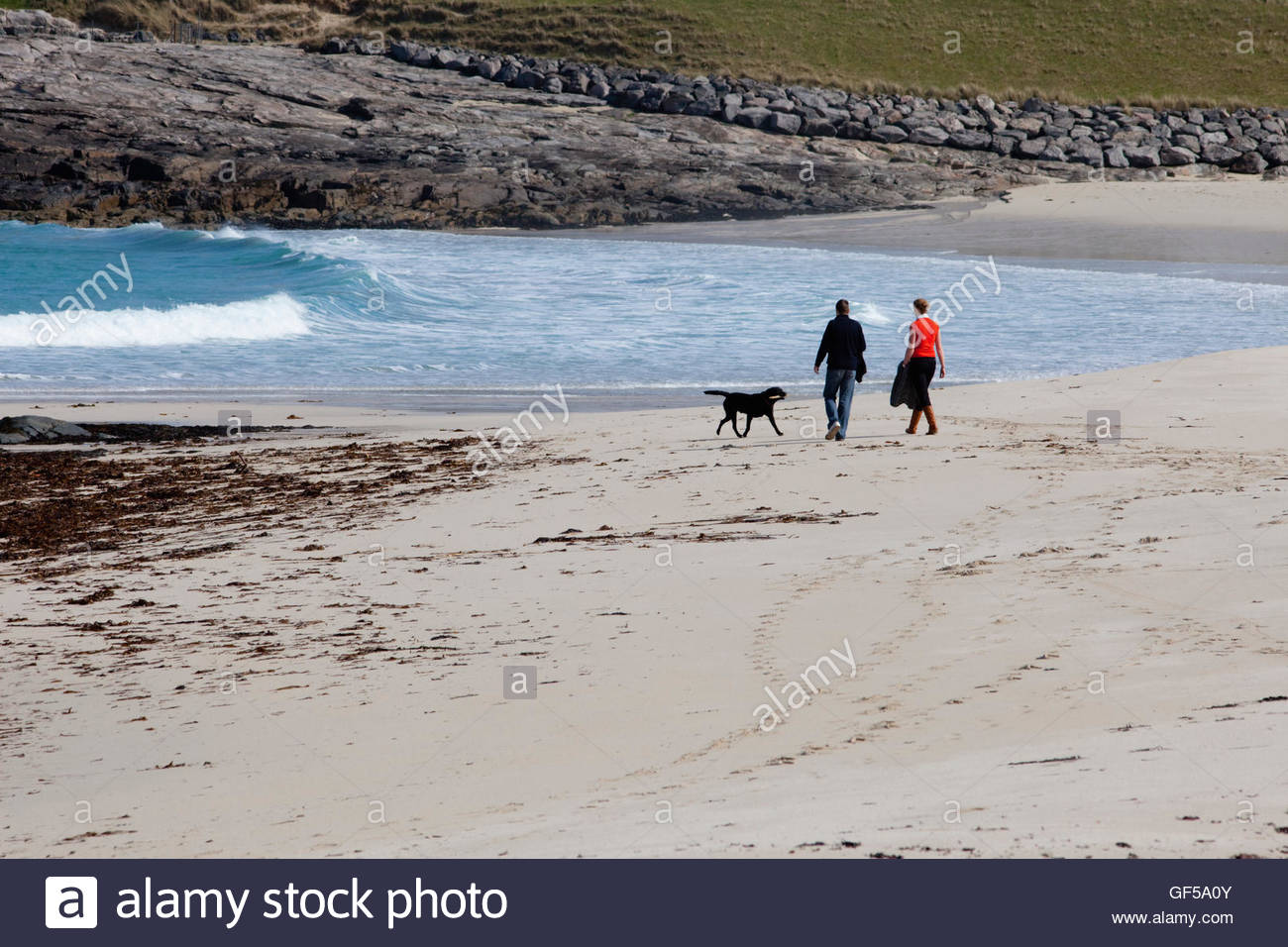 A couple walking their dog on Tangasdale Beach, Isle of Barra, Outer Hebrides.  Scotland - Stock Image