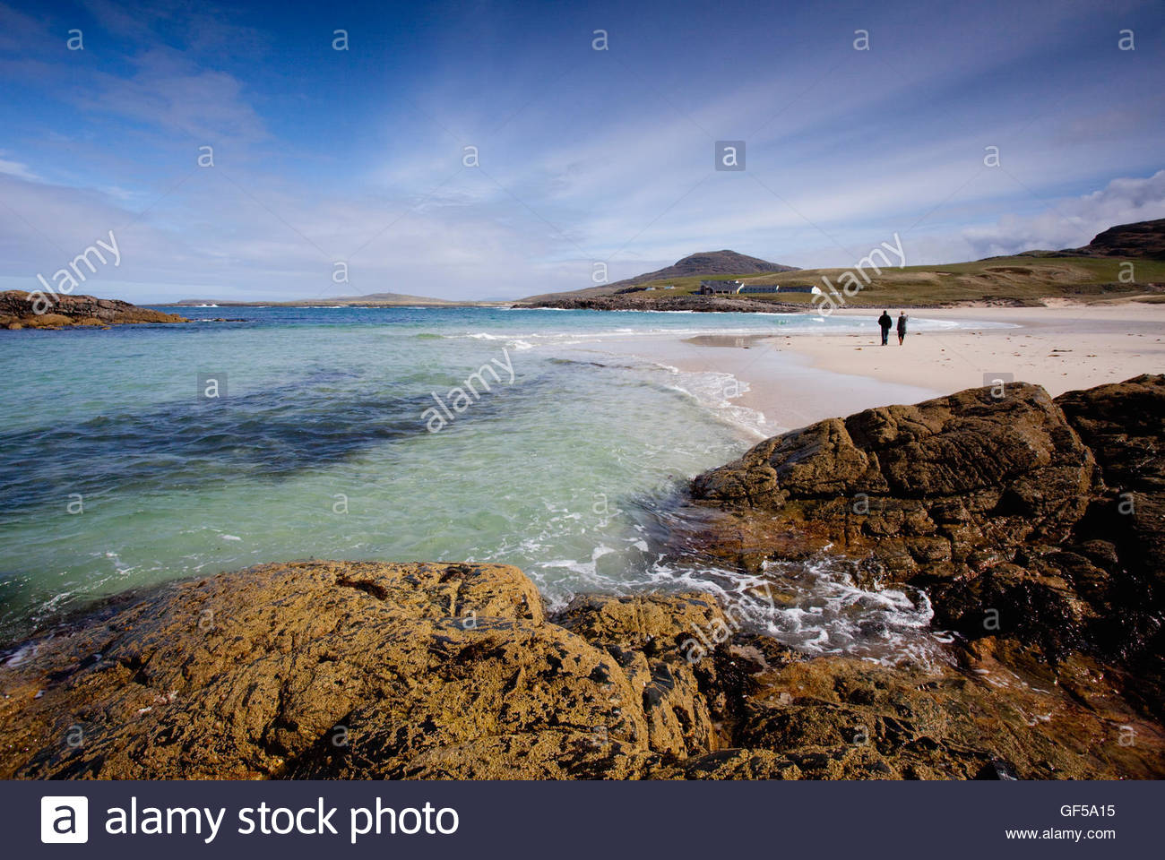 A couple walking on Tangasdale Beach, Isle of Barra, with a view beyond to the Isle of Barra Hotel, Outer Hebrides. - Stock Image