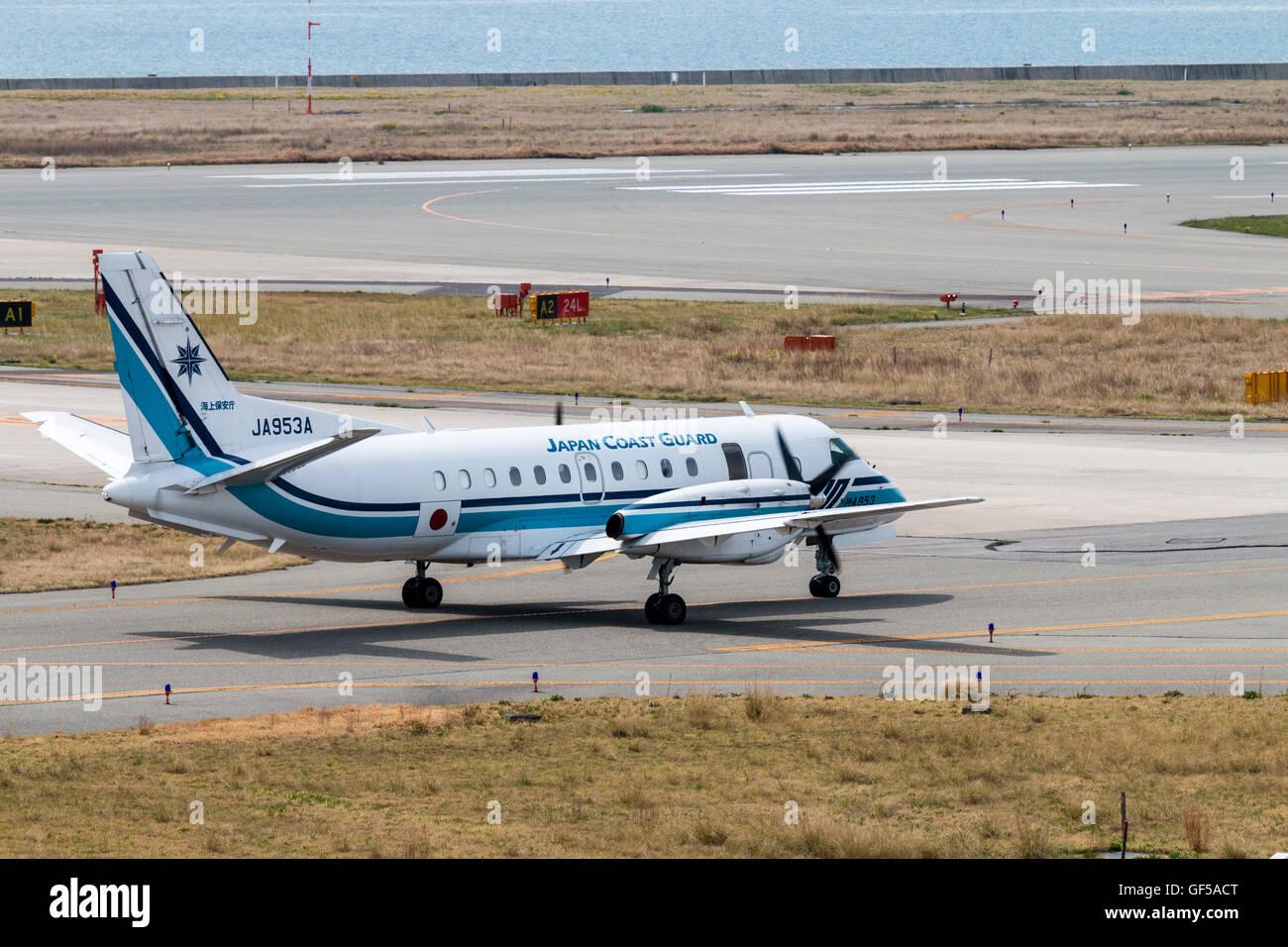 Japan, Osaka, Kansai airport, KIX. Japanese Coast Gaurd SAAB 340, JA953A, turboprop airplane with engines running - Stock Image