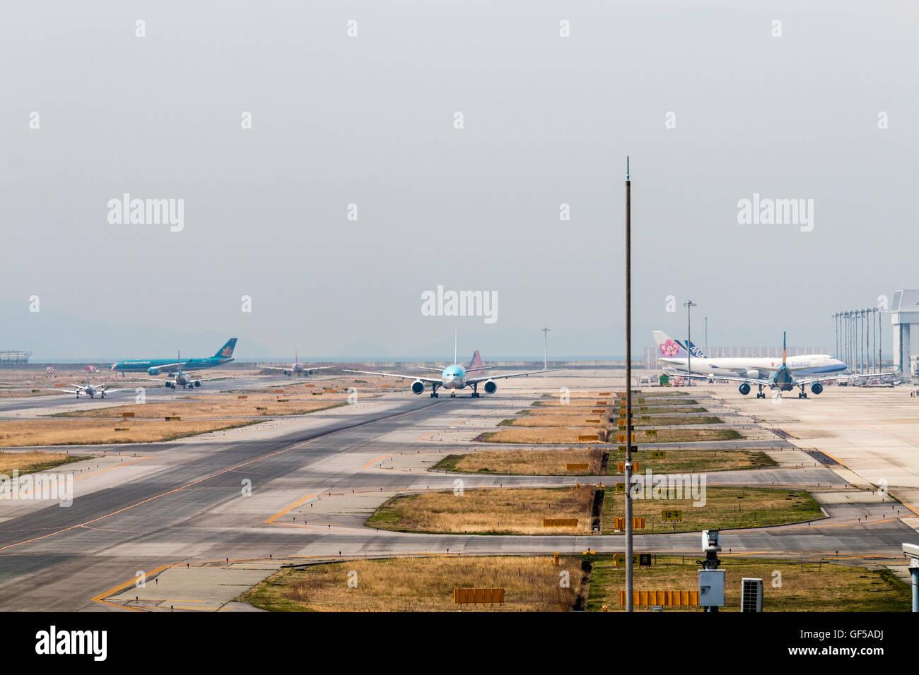 Japan, Osaka, Kansai airport, KIX. 'KLM Asia' 777-206ER taxiing on runway. Another aircraft taxiing along - Stock Image