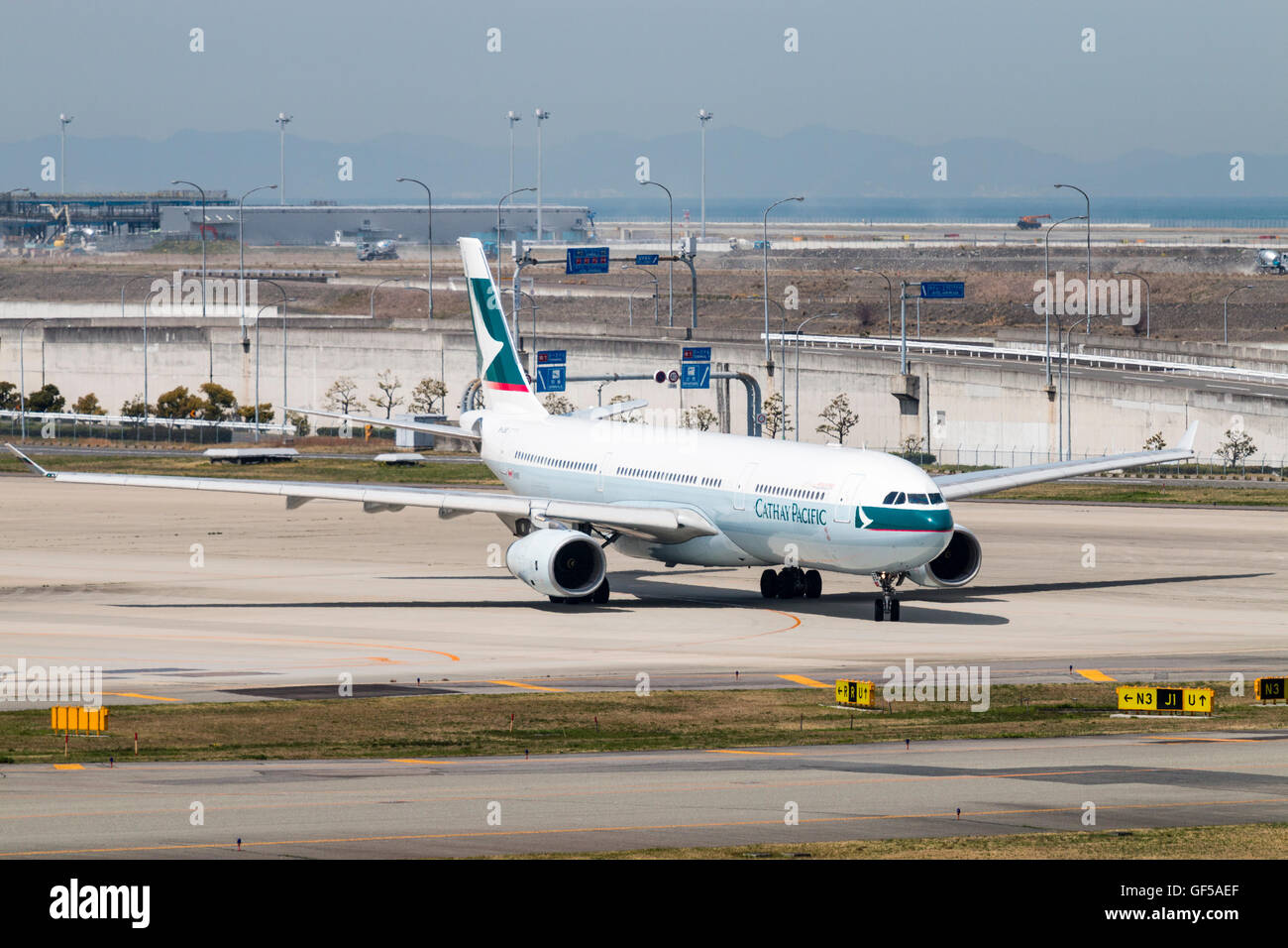 Japan, Kansai airport, KIX. Cathay Pacific Boeing 777-300 ER, B-LBE, taxiing and turning on apron around main runway. - Stock Image