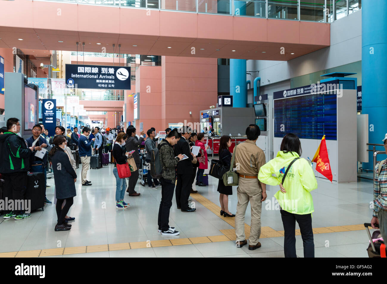 Kansai airport, Japan. Interior, terminal 1. General view of ground floor with many people standing looking at the - Stock Image