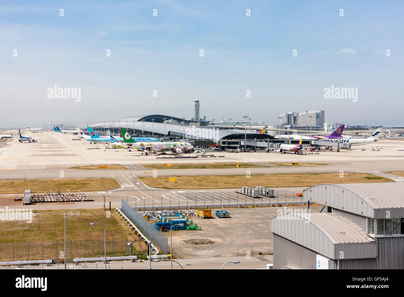 Japan, Kansai airport, KIX. Distant view of terminal one with various planes parked from the observation lounge - Stock Image