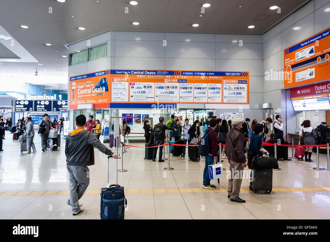 Japan, Kansai airport, KIX. Interior Aeroplaze transport hub. Nankai railways ticket area with passengers, some - Stock Image