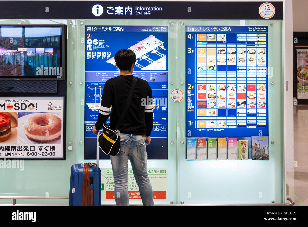 Japan, Kansai airport, KIX. Terminal interior. Domestic check-in hall. Asian man with suitcase reading second floor - Stock Image